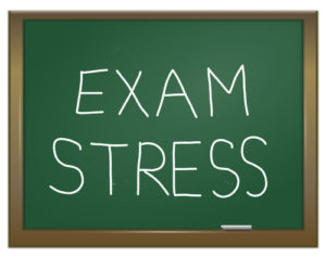Illustration depicting a green chalk board with the words 'exam stress' written on it in white chalk.